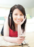 Jolly woman listening music with headphones on lyi Stock Photography