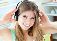 Jolly woman listening to music with headphones. Jolly caucasian woman listen to music with headphones in the kitchen Royalty Free Stock Photo