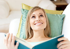 Jolly woman reading a book lying on a sofa Royalty Free Stock Image