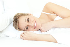 Jolly woman relaxing lying on a bed Royalty Free Stock Photo