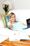 Jolly woman surfing the internet lying on a sofa. At home Royalty Free Stock Photo