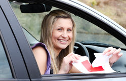 Jolly young female driver tearing up her L sign royalty free stock image