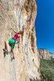 Jolly Young Girl accrochant sur le paysage ensoleillé de mur rocheux vertical Photo stock