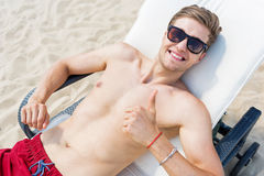 Jolly young guy having pleasure time while sunbathing outdoor Stock Photos