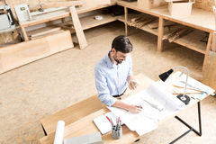 Jolly young lumber designer working on produce model in workshop Royalty Free Stock Photos