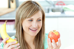 Jolly young woman holding an appke and a banana. Sitting in the kitchen Royalty Free Stock Photography