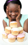 Jolly young woman looking at cakes Royalty Free Stock Photo