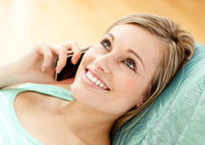 Jolly young woman talking on phone lying on a sofa Stock Photos
