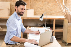 Jolly youthful lumber craftsman using modern gadget in his job Stock Images