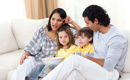 Jollyfamily watching TV on sofa Royalty Free Stock Image
