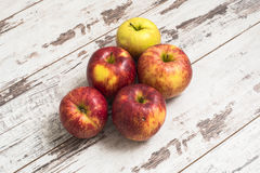 Jonagold äpplen på den målade trätabellen Arkivbilder