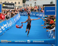 Jonathan Brownlee with flag - finish. STOCKHOLM - AUG 23, 2014: Jonathan Brownlee waving a flag in the finish of the race only a few yards before his brother in Royalty Free Stock Images