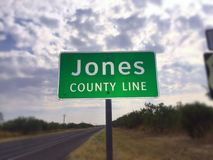 Jones County Texas. A party cloudy day on the road. The Jones county line sign in West Texas caught my attention & so did the Texas Highway Patrol as they wrote Stock Photography