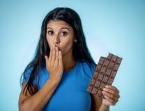 Jong aantrekkelijk brunette die vreugde en schuld voelen bij de gedachte van het eten van chocolade royalty-vrije stock foto's