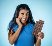 Jong aantrekkelijk brunette die vreugde en schuld voelen bij de gedachte van het eten van chocolade stock fotografie