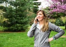 Jong aantrekkelijk brunette op celtelefoon in park royalty-vrije stock afbeeldingen