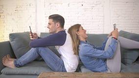 Jong aantrekkelijk en gelukkig paar die Internet app op mobiele en telefoon gebruiken die samen het zitten rijtjes thuis van c ge stock afbeeldingen