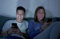 Jong aantrekkelijk en gelukkig paar die Internet app op mobiele en telefoon gebruiken die zo thuis samen zittend woonkamer geniet Stock Fotografie