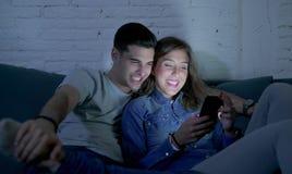 Jong aantrekkelijk en gelukkig paar die Internet app op mobiele en telefoon gebruiken die zo thuis samen zittend woonkamer geniet Stock Afbeeldingen