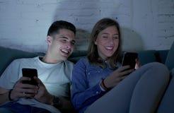 Jong aantrekkelijk en gelukkig paar die Internet app op mobiele en telefoon gebruiken die zo thuis samen zittend woonkamer geniet Stock Afbeelding