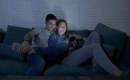 Jong aantrekkelijk en gelukkig paar die Internet app op mobiele en telefoon gebruiken die zo thuis samen zittend woonkamer geniet Stock Foto's