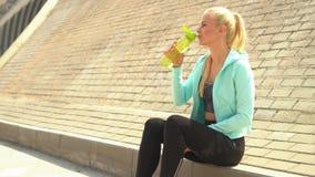 Jong, aantrekkelijk en sportief blond meisje in sportkleding openlucht ontspannen Gezondheidszorg, sport, fitness en levensstijl stock video