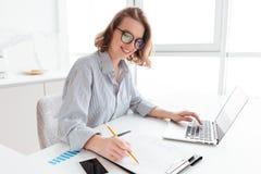 Jong aantrekkelijk glimlachend meisje in glazen en gestreepte overhemdsworki stock fotografie