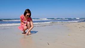 Jong aantrekkelijk het hartteken van de vrouwentekening op een eenzaam zandig strand met sterke golven die de kust raken Zij draa stock videobeelden