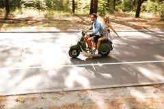 Jong aantrekkelijk houdend van paar op autoped in openlucht Opzij het kijken stock afbeeldingen