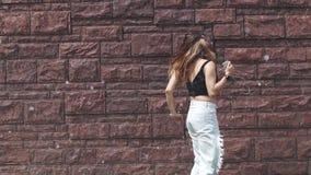 Jong aantrekkelijk meisje die aan muziek op hoofdtelefoons luisteren en op de straat dansen het meisje loopt cheerfully rond de s stock videobeelden
