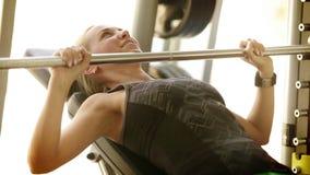 Jong aantrekkelijk meisje die een barbell die in gymnastiek opheffen haar borstspieren werken stock footage