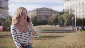 Jong aantrekkelijk meisje in een stadspark met een telefoon in een de zomerdag stock videobeelden