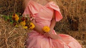 Jong aantrekkelijk meisje in een strohoed die en bij de camera op de achtergrond van hooi met wildflowers stellen glimlachen 4K 4 stock video