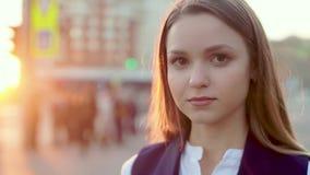 Jong aantrekkelijk meisje, in het avond stedelijke landschap die, nadenkend, aan de camera kijken stock video