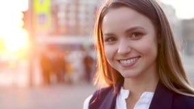 Jong aantrekkelijk meisje, in het avond stedelijke landschap, glimlachen, die aan de camera kijken stock video