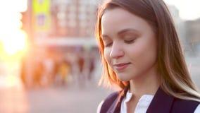 Jong aantrekkelijk meisje, in het avond stedelijke landschap, glimlachen, die aan de camera kijken stock videobeelden