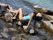 Jong aantrekkelijk meisje op de stenen Stock Foto's