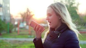 Jong aantrekkelijk meisje op de straat, ingesproken berichtboodschapper stock video