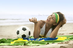 Jong aantrekkelijk meisje op strand met de vlag en de voetbal van Brazilië Royalty-vrije Stock Fotografie