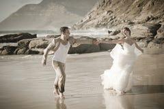 Jong aantrekkelijk paar die langs strand flirten die wit dragen royalty-vrije stock fotografie