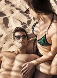 Jong, aantrekkelijk paar die op een tropisch strand rusten royalty-vrije stock afbeeldingen