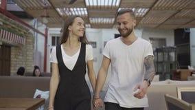 Jong aantrekkelijk paar die samen en in langzame motie van 100fps glimlachen lopen stock footage