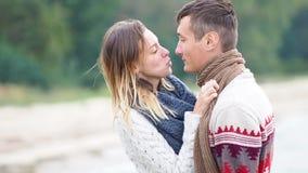 Jong aantrekkelijk paar in gebreide sweaters op een klip bij het overzeese kust, het plagen, het koesteren en kussen stock video