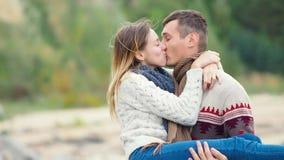 Jong aantrekkelijk paar in gebreide sweaters op een klip op overzeese kust, plagend, koesterend en kussend, mensengolven zijn mei stock footage
