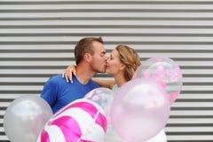 Jong aantrekkelijk paar in liefdekussen op gestreepte achtergrond en colorfull ballons Royalty-vrije Stock Fotografie