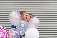 Jong aantrekkelijk paar in liefdekussen op gestreepte achtergrond en colorfull ballons Royalty-vrije Stock Foto