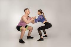 Jong aantrekkelijk paar in in sportkleding die sguats samen doen royalty-vrije stock afbeeldingen