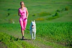 Jong aantrekkelijk sportmeisje die met hond in park lopen Stock Afbeelding