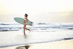 Jong aantrekkelijk surfermeisje met raad die uit aan de golven lopen Stock Foto's