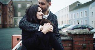 Jong aantrekkelijk toeristenpaar die en in een romantische bestemmingsstad omhelzen kussen 4K stock footage